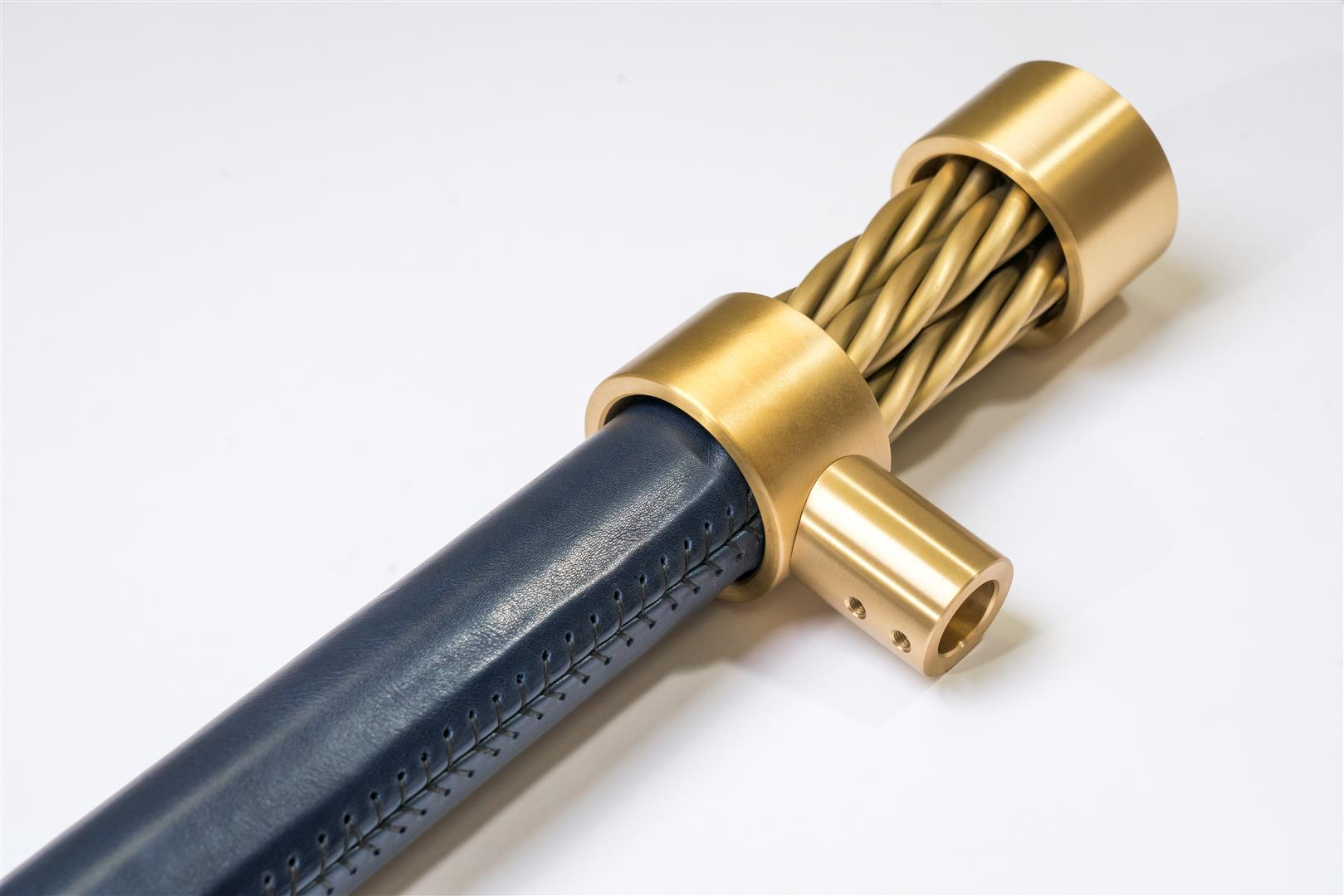 Leather and buffed brass make an excellent combination for door handles and other hardware. Navy Blue Long Wearing Leather shown here with lacquered brass.